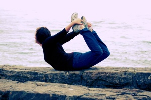 Me in Dhanurasana (Bow Pose) on a cliff overlooking the ocean on the Oregon Coast.